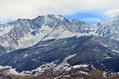 Steniga snö-korkade berg över byn av Fiagdon arkivfoto