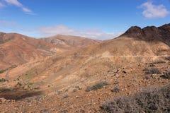 Stenigt kullelandskap med vägen i Fuerteventura arkivfoton