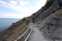 Stenigt land nära havet På lutningen av en av klipporna finns det en grusväg som turister går längs royaltyfri bild