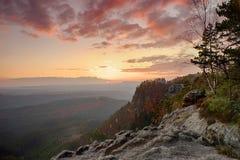 Stenigt landskap för höst inom solnedgång Färgrik himmel ovanför den djupa dimmiga dalen mycket av aftonfuktighet Sol på horisont Arkivbild