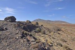 Stenigt landskap med vulkaniska kullar i bakgrunden Royaltyfri Foto