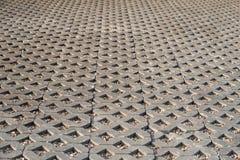 Stenlägga den gråa tegelplattan i en romb, sand i en tegelplatta i form av en triangel, texturen av tegelplattan royaltyfria bilder
