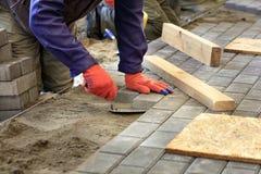Stenlägga tegelplattorna på trottoaren, lägger arbetaren tegelplattan som arrangera i rak linje den på tråden arkivbilder