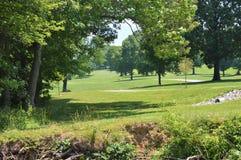 Stenlade banor som passerar till och med ett grönt fält med åtskilliga högväxta träd royaltyfria bilder