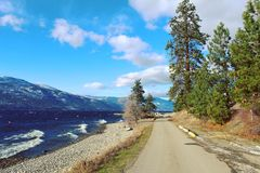 Stenlagd väg längs den sceniska sjön Arkivfoto