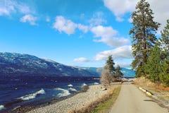Stenlagd väg längs den sceniska sjön Royaltyfria Foton