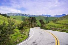 Stenlagd väg som går till och med grönskande kullar, montering Hamilton i bakgrunden, södra San Francisco Bay, San Jose, Kaliforn arkivfoton