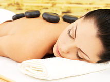 Stenmassage för kvinna på brunnsortsalongen. Arkivfoton