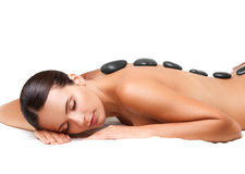 Stenmassage. Härlig kvinna som får Spa varm stenmassage. S Royaltyfri Bild