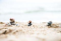 Stenpyramider på sand Hav i bakgrunden Royaltyfria Bilder