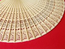 Stensiled wooden fan. Beautifully stensiled Carved wooden japanese fan on red velvet cloth Royalty Free Stock Images