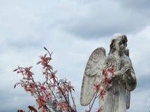 Stenstaty av en ängel med vingar som ber royaltyfri bild