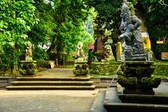Stenstaty av guden som bevakar den sakrala templet med färgrik traditionell cloting royaltyfri bild