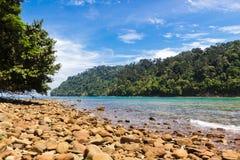 Stenstrand på en tropisk ö Royaltyfria Bilder