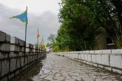 Stenvägg med balustrader och flaggor i molnig våreftermiddag royaltyfri bild