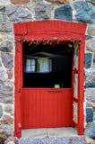 Stenvägg med den röda ladugårddörren arkivfoto