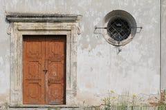 Stenvägg med en gammal trädörr och ett litet fönster royaltyfri bild