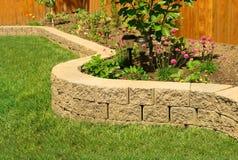 Stenvägg med perfekt gräs som landskap i trädgård med konstgjort gräs royaltyfri bild