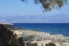 Stenvägg nära havet och bergen Arkivbild