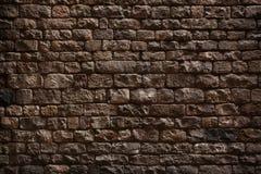 Stenvägg som göras av grova tegelstenar Arkivfoto