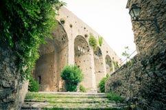 Stenväggar, bågar, trappa, lampa och gröna dingla växter av det forntida Castello Doria slotttornet i Portovenere arkivbild