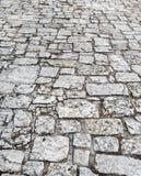 Stenvägslut upp Gammal trottoar av granit Grå kullerstentrottoar Övre åtlöje eller tappninggrungetextur arkivfoton