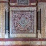 Stenv?gg som dekoreras med f?rgrika inristade blom- och geometriska modeller p? ing?ngen av den Sultan Hassan mosk?n, Kairo, Egyp royaltyfri foto