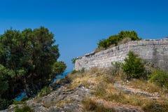 Stenväggar av den forntida fästningen upp kullen Arkivfoto