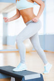 Step aerobics. Cropped image of beautiful young woman in sports clothing doing step aerobics while in health club Stock Photography