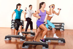Step aerobics with dumbbells. People with dumbbells on step boards in gym Stock Images