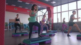 Step aerobics exercise class - group of people exercising on steppers with the trainer. stock footage