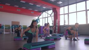 Step aerobics exercise class - group of people exercising on steppers with the trainer. stock video footage
