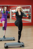Step aerobics in gym with dumbbells Stock Image