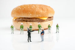 Step Away from the Burger!. Tiny police preventing an overweight man from reaching a burger a public health obesity concept selective focus on foreground figures Stock Photography