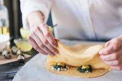 Step by step the chef prepares ravioli with ricotta cheese, yolks quail eggs and spinach with spices. The chef prepares the fillin. G on the dough Stock Photo