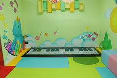 Step on floor piano in play room. Bright pastel colored geometric designed playroom with step on floor piano Royalty Free Stock Image