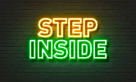Step inside neon sign on brick wall background. Stock Image