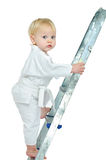 On step ladder. Little boy in kimono on step ladder and white background Royalty Free Stock Images
