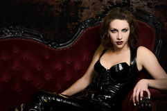Step into my Lair - Female Vampire in Catsuit. Beautiful young woman in latex catsuit on classic red couch Stock Images