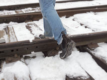 Step over the rails, walk on the sleepers. In winter in the boots Royalty Free Stock Image