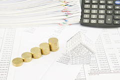 Step pile of gold coins and house on balance sheet Stock Image