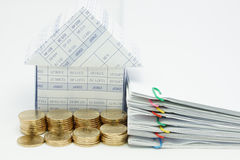 Step pile of gold coins and house. With pile overload document of report with colorful paperclip on white background stock photo