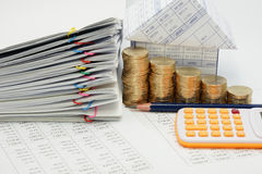Step pile of gold coins and pile overload document. With colorful paperclip and house with pencil and calculator on finance account with white background Stock Photos