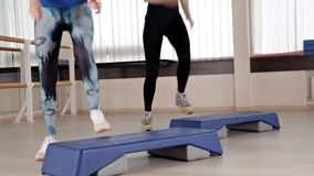 Step platforms. Girls in sports shoes doing exercises for aerobics. The concept of tightening in the gym for weight loss