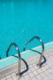 Step into the pool. Stairs leading into swimming pool Stock Photography