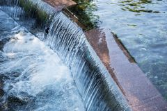 Step with running water. Artificial small waterfall. The symbol of the current of life royalty free stock photo