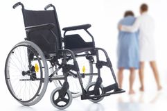 Step by step. Nurse helping a patient to walk away from his wheelchair Royalty Free Stock Images