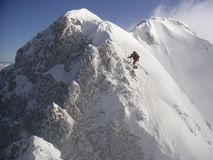 Step by step. Climber asscending the mountain in full action, wind is blowing the snow away making a breathtaking alpine scene Stock Image