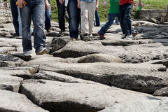 Step by step. Tourist feet at an ancient roman road Stock Images