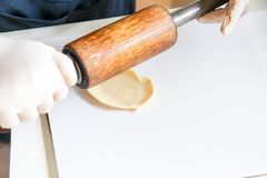 Step by step, baker prepares bread. baker slaps on dough. making bread, hand with rolling pin and flour stock images